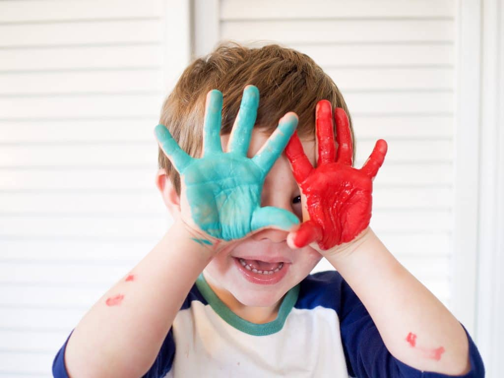 Kid with colorful handprints